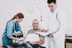 Gente en hospital El doctor y enfermera Help Old Man imagen de archivo