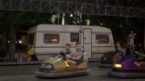 Gente en la atracción de los coches de parachoques en parque de atracciones al aire libre almacen de video