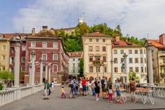 Gente en la calle de la ciudad vieja en Ljubljana en el fondo de edificios viejos hermosos y de un castillo Imágenes de archivo libres de regalías