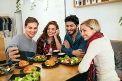 Gente en la cena que toma las fotos en el teléfono Vídeo de los amigos llamada imagen de archivo