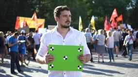 Gente en la demostración con una bandera Cartelera verde con el marcker para seguir metrajes