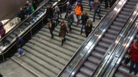 Gente en la escalera móvil y la escalera rápidas hacia arriba y hacia abajo almacen de metraje de vídeo