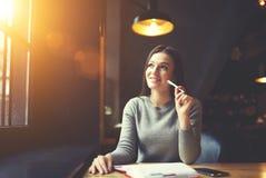 Gente en la escritura del trabajo en el cuaderno que se sienta en café Foto de archivo libre de regalías