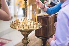 Gente en la iglesia puesta velas encendidas foto de archivo libre de regalías