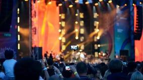 Gente en la muchedumbre que hace los vídeos con la etapa del concierto al aire libre en sus smartphones almacen de video