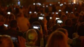 Gente en la muchedumbre que hace los vídeos y las fotos de fuegos artificiales en sus smartphones almacen de metraje de vídeo