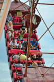Gente en la nave de balanceo bajo el cielo nublado azul Foto de archivo libre de regalías