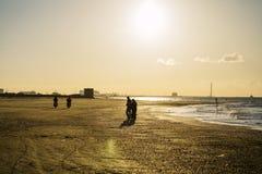 Gente en la playa en el tiempo de la puesta del sol imagen de archivo