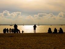 Gente en la playa en la puesta del sol imagen de archivo