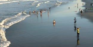 Gente en la playa en la puesta del sol Fotografía de archivo libre de regalías