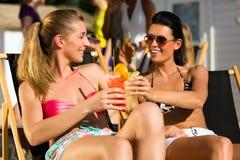Gente en la playa que bebe teniendo un partido Foto de archivo