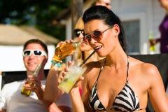 Gente en la playa que bebe teniendo un partido Imagenes de archivo