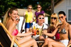 Gente en la playa que bebe teniendo un partido Imágenes de archivo libres de regalías