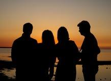 Gente en la playa y la puesta del sol Foto de archivo libre de regalías