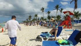 Gente en la playa y las palmeras que agitan en el viento, Bahamas almacen de metraje de vídeo