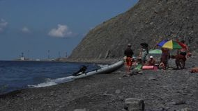 Gente en la playa y un barco de motor almacen de video