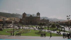 Gente en la plaza principal Cuadrado con la iglesia, Cuzco, Perú almacen de video