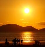Gente en la puesta del sol de oro de la playa Fotos de archivo libres de regalías