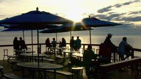 Gente en la puesta del sol 1 del café del océano metrajes