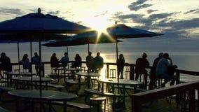 Gente en la puesta del sol del café del océano metrajes