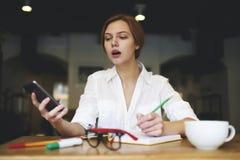 Gente en las últimas noticias del trabajo usando smartphone Imagen de archivo