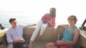 Gente en las cervezas de consumición del yate mientras que habla - grupo de amigos que tienen partido en el barco de navegación metrajes