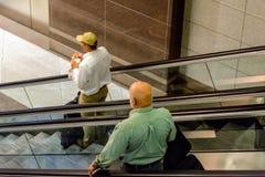 Gente en las escaleras móviles en un aeropuerto Fotografía de archivo