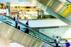 Gente en las escaleras móviles en un aeropuerto Fotografía de archivo libre de regalías