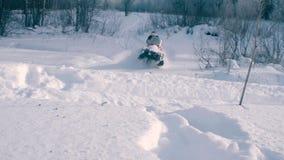 Gente en las motos de nieve que montan en el bosque del invierno Foto de archivo