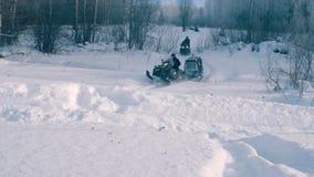 Gente en las motos de nieve que montan en el bosque del invierno Fotografía de archivo libre de regalías