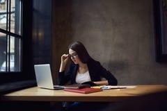 Gente en las reacciones del trabajo con las marcas usando el ordenador portátil y el wifi Imagen de archivo