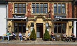 Gente en las tablas fuera de restaurantes en la sol imagenes de archivo