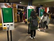 Gente en los quioscos del servicio del uno mismo en un McDonalds en Hong Kong Fotos de archivo