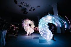 Gente en los trajes que brillan intensamente que bailan en la oscuridad foto de archivo