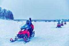 Gente en móviles de la nieve, invierno Finlandia fotos de archivo