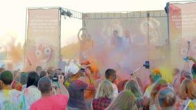 Gente en polvo coloreado que disfruta de música en el concierto del holi, krishna de los devotos, festival del aire abierto, kris almacen de video