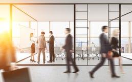 Gente en sala de reunión con las paredes de cristal Imágenes de archivo libres de regalías