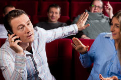 Gente en teatro del cine con el teléfono móvil Fotografía de archivo