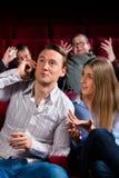 Gente en teatro del cine con el teléfono móvil Imagen de archivo