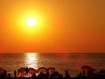 Gente en tiempo de la puesta del sol en la playa Imágenes de archivo libres de regalías