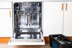 Gente en trabajos del t?cnico Un lavaplatos incorporado quebrado con la puerta abierta en una cocina blanca y la caja de herramie fotos de archivo libres de regalías