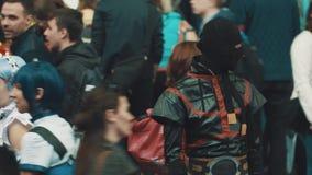 Gente en trajes de los caracteres del animado en el festival cosplay apretado metrajes