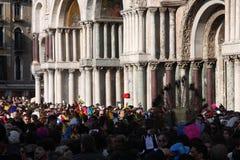 Gente en trajes delante de la basílica San Marco de la basílica del ` s de St Mark en Venecia, Italia durante el carnaval de Vene Foto de archivo libre de regalías