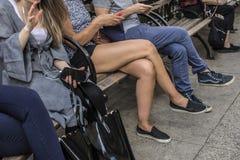 Gente en un banco de parque usando allí smartphones y la charla foto de archivo libre de regalías
