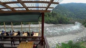 Gente en un café que pasa por alto el río que corre con el paisaje verde de Rize en la región del Mar Negro, Turquía de Firtina almacen de video
