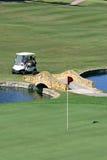 Gente en un cochecillo del golf que llega el verde Imagen de archivo