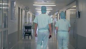Gente en un edificio de la clínica Hombre y mujer que caminan con un vestíbulo vacío en hospital almacen de metraje de vídeo