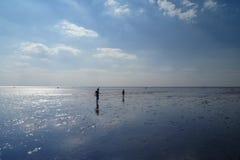 Gente en una playa en marea inferior Fotos de archivo