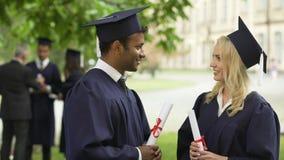 Gente en vestido y sombreros académicos con los diplomas en manos que habla, día de graduación almacen de video