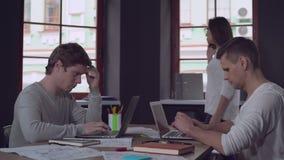 Gente enfocada casual que trabaja con el ordenador metrajes